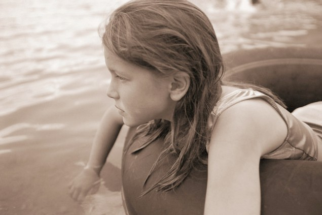 ca. 2001 --- Girl Floating on Inner tube --- Image by © Royalty-Free/Corbis